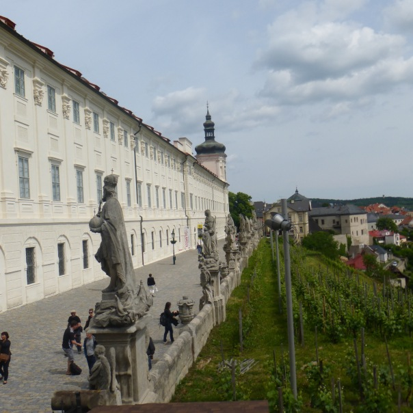 cobblestone pathway to town lined with statues overlooking vineyards